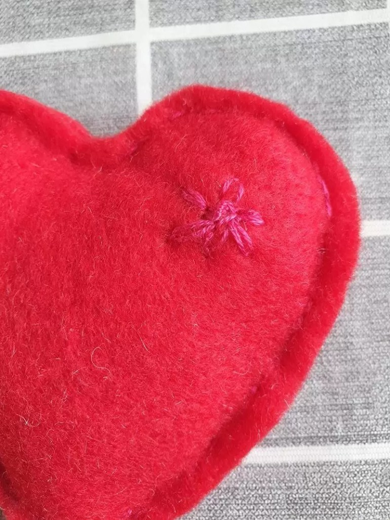 stitched flower on red felt heart close up