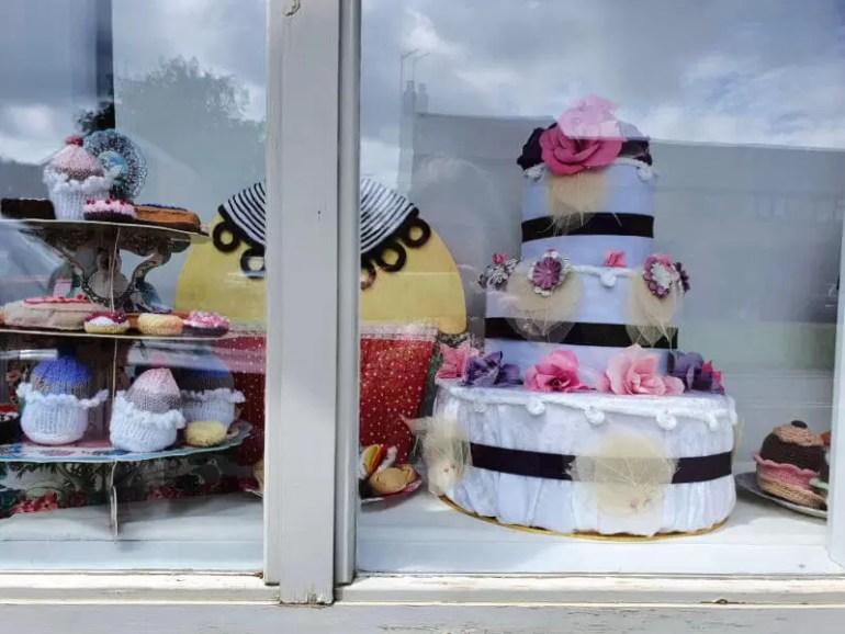 Yarn crafts in window at village shop
