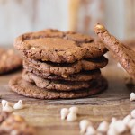 Salted Caramel Chocolate Cookies sitting on a table with chocolate and caramel chips