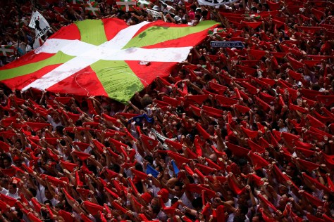 """Revellers hold up their red scarves next to a Basque Country flag during the start of the San Fermin Festival in Pamplona July 6, 2012. The annual festival, best known for its daily running of the bulls, kicked off on Friday with the traditional """"Chupinazo"""" rocket launch and will run until July 14. (Susana Vera/Reuters photo)"""