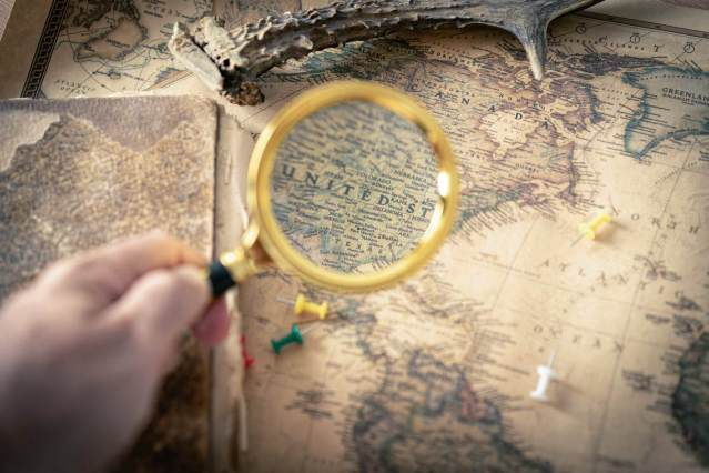 A person is holding magnifying glass to know more about a country on a map