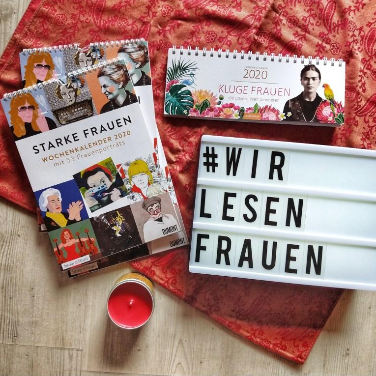 """das Bild zeigt drei Kalender mit dem Titel """"starke Frauen"""" von Dumont auf einem roten Schal. Unten steht eine rote Kerze. Rechts ist ein Tischkalender mit dem Titel """"kluge Frauen"""" und darunter eine Lightbox mit #WirlesenFrauen"""