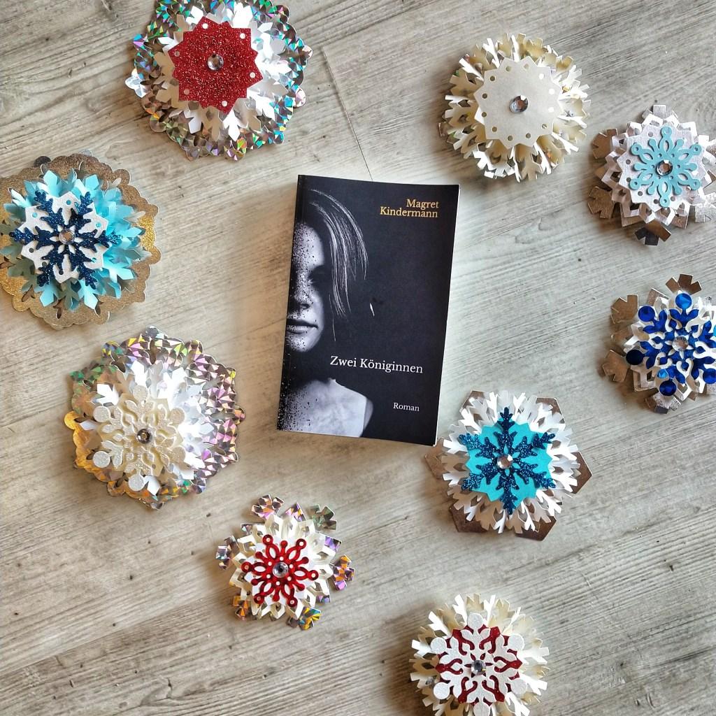 """Das Buch """"zwei Königinnen"""" von Magret Kindermann, umringt von glitzernden Schneeflocken aus Papier, auf einem Hintergrund aus hellem Holz"""