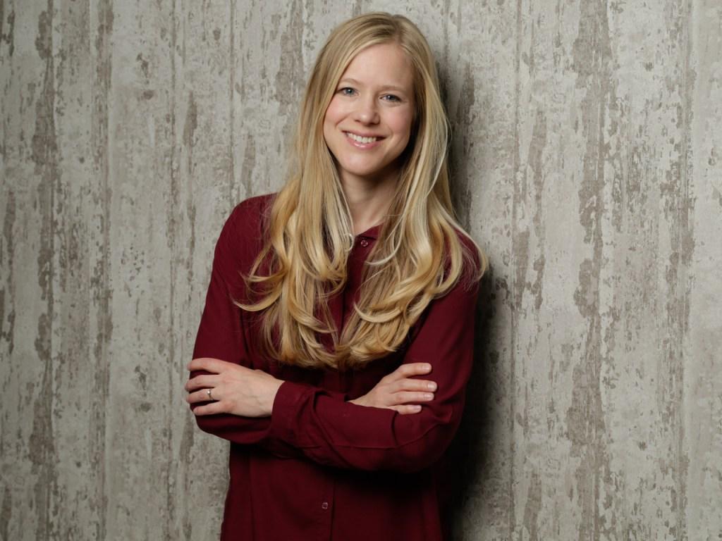 Anja Kiel, lange, blonde Haare mit roter Bluse, lacht in die Kamera