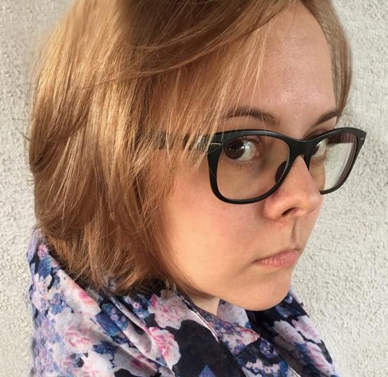 Laura Meyer, eine junge Frau mit schwarzer Bille, hellbraunen schulterlangen Haaren und einem Schal mit Blumenmuster