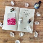 """Das Buch liegt offen mit der Titelei, der Titel des Buches und die Autorin, sowie der Verlag sind zu lesen. Sommergäste von Agnes Krup, erschienen bei Piper. Darum sind weiße Blütenblätter verstreut und drei Tonvögel gesetzt. Eine Karte mit dem Spruch """"Do what you love"""" liegt auf dem Buch."""