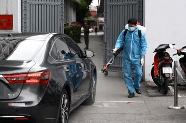 Un hombre, vestido con un traje de protección como medida preventiva contra la propagación del nuevo coronavirus, rocía desinfectante en un automóvil en Hanoi el 1 de abril de 2020