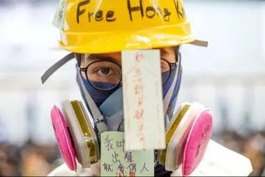 Una manifestante, con caso y máscara antigás en el aeropuerto de Hong Kong