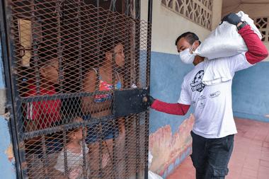 Un voluntario entrega comida en los barrios más humildes de Panamá