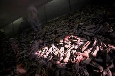 A 75 años de la liberación de los detenidos en Auschwitz, una persona recorra la muestra donde se exhiben zapatos de los prisioneros