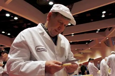 El juez Christophe Megevand inspecciona un pedazo de queso Gruyere en el Concurso Mundial de Queso del Campeonato Mundial, el martes 3 de marzo de 2020, en el Centro de Convenciones Monona Terrace en Madison, Wisconsin. Es la competencia técnica de queso, mantequilla y yogurt más grande del mundo.