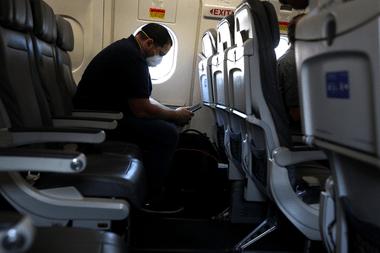 Un pasajero con barbijo mira su teléfono mientras espera a bordo de un avión de United Airlines antes de despegar del Aeropuerto Intercontinental George Bush el 11 de mayo de 2020 en Houston, Texas