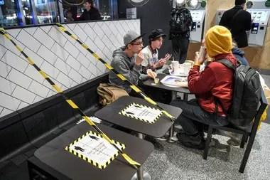 Jóvenes en un restaurante de comida rápida junto a mesas separadas en el centro de Estocolmo, el 12 de noviembre de 2020