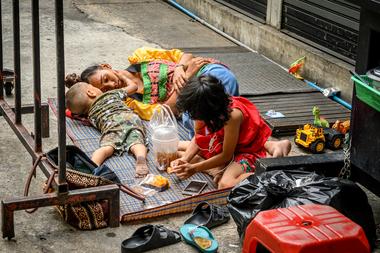 Una vendedora de comida callejera descansa mientras sus hijos juegan detrás de su carrito después de que se levantaran las restricciones para detener la propagación del coronavirus en Bangkok, Tailandia, el 18 de mayo de 2020