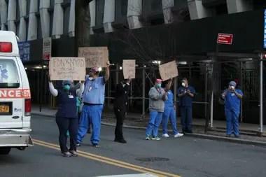 Médicos, enfermeros y otros profesionales de la salud alzan carteles en agradecimiento