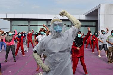 Un instructor de gimnasia con equipo de protección personal dirige un ejercicio matutino para pacientes del coronavirus en un hotel designado para tratar pacientes asintomáticos en Karawaci, en Indonesia, el 5 de octubre de 2020
