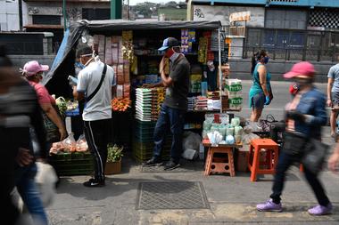 En esta foto de archivo tomada el 2 de abril de 2020, las personas usan mascarillas en un mercado como medida preventiva contra la propagación del nuevo coronavirus, en el barrio de Petare en Caracas