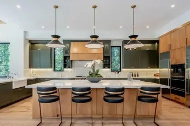 La cocina de la mansión es moderna y tiene una mesa de mármol y oro