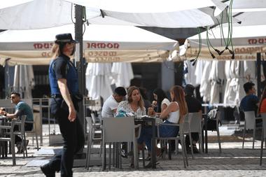 Las personas se sientan en un bar en la Plaza Mayor de Madrid el 25 de mayo de 2020, luego de que las medidas de bloqueo del coronavirus finalmente se flexibilizaron para las personas en Madrid y Barcelona