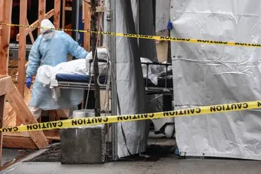Un trabajador de un hospital en Brooklyn retira el cuerpo de un fallecido del establecimiento para almacenarlo en un camión refrigerado