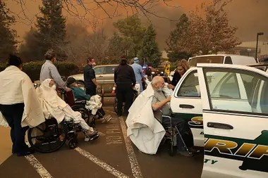 Trabajadores del hospital y socorristas evacuan a los pacientes del hospital Feather River en Paradise, California.