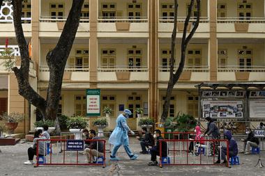 Los residentes, que usan mascarillas como medida preventiva contra la propagación del coronavirus, practican el distanciamiento social mientras esperan ser examinados en un improvisado centro de pruebas rápidas cerca del hospital Bach Mai en Hanoi el 31 de marzo de 2020