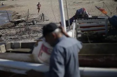 Los vecinos de José Ignacio cruzan por el pequeño puerto mientras los pescadores llegan tras ocho horas en el mar