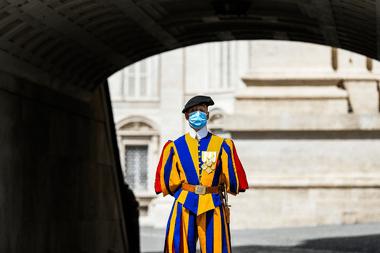 En esta foto de archivo tomada el 18 de mayo de 2020, un guardia suizo con una mascarilla hace guardia junto a la Basílica de San Pedro