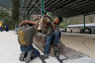 Niños con juguetes y armas reales, demuestran habilidades recién aprendidas del entrenamiento con armas de estilo militar