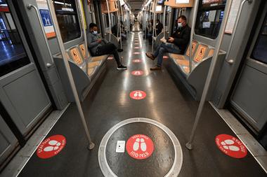 Los autobuses en Milán tienen etiquetas rojas en el piso que marcan la distancia entre los pasajeros en plena pandemia de coronavirus