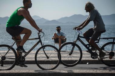 Las personas circulan en bicicleta y llevan mascarillas en Río de Janeiro, Brasil