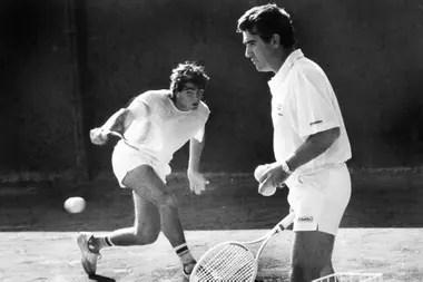 Guillermo Pérez Roldán pega un revés, bajo la mirada de Raúl, durante una pretemporada en Tandil en los 80