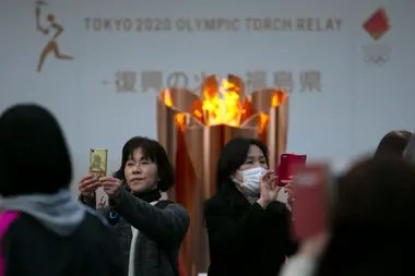 In this archive photo from march 24, 2020, people take photos with the Olympic Flame during a ceremony in the city of Fukushima, Japan.