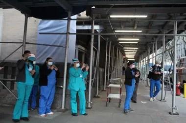 Médicos, enfermeros y otros profesionales de la salud reciben los aplausos de los vecinos y los bomberos
