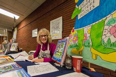 """Illustrator Liz Ball signs her """"Hidden Treasures Picture Puzzles."""