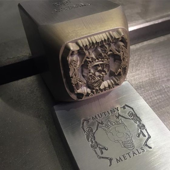 custom logo stamp for Mutiny Metals Silver Stamp shows two dancing skeletons on each side of skull wearing crown