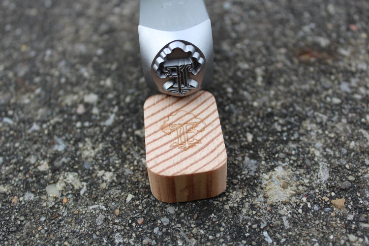 steel wood hand stamp for marking wood made by Buckeye Engraving pictured showing stamp's tree design deeply engraved in steel hand stamp and pied of end grain wood shows stamp image on it