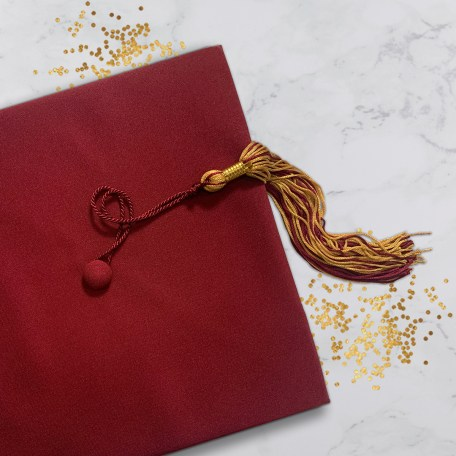 maroon graduation cap with maroon and gold tassel