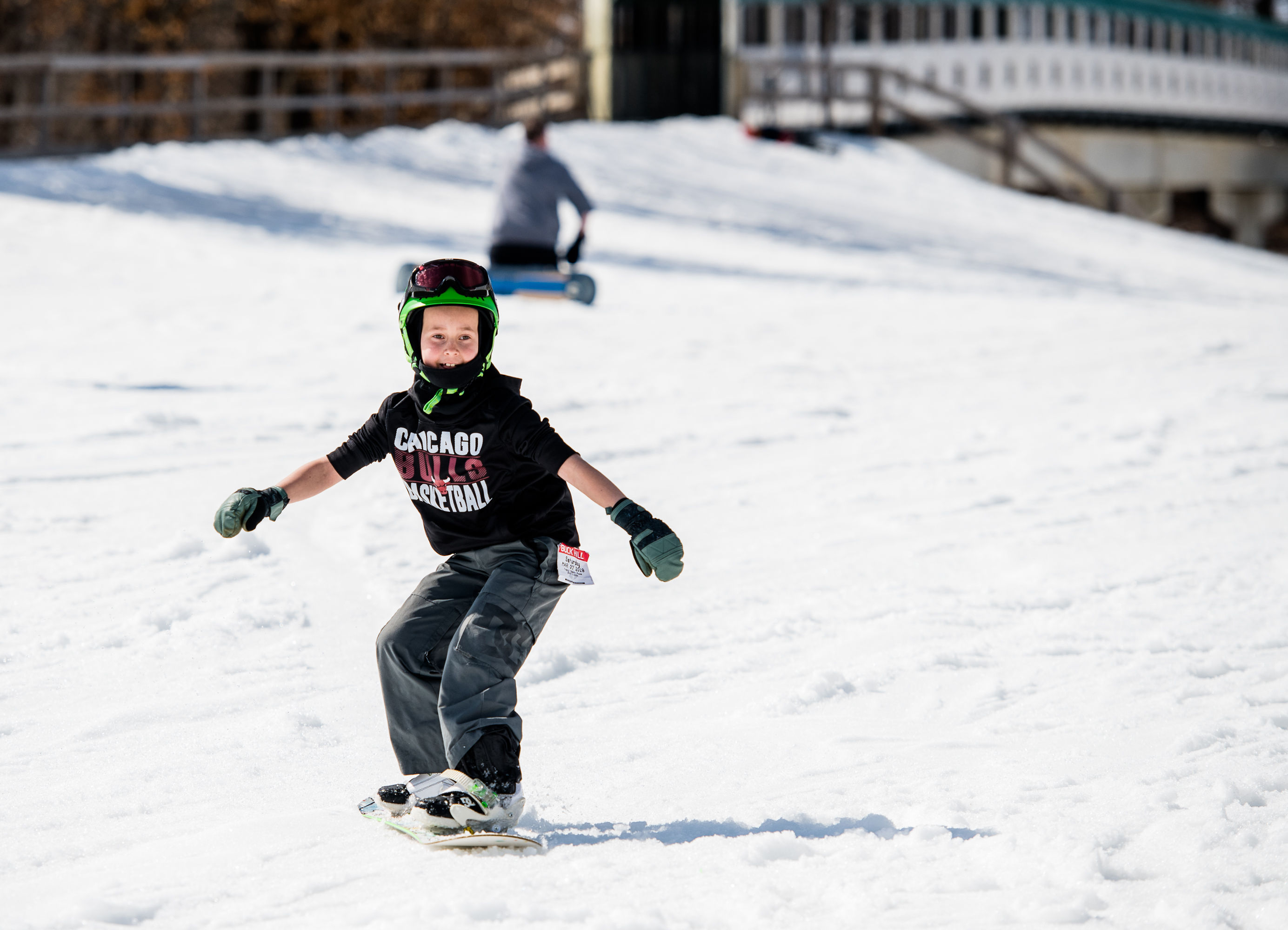 Child snowboarding down a snow hill