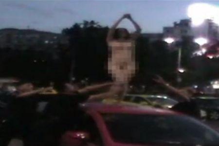 FOTO- O femeie s-a urcat dezbracata complet pe o masina, intr-o intersectie din Bucuresti, si a refuzat sa coboare!