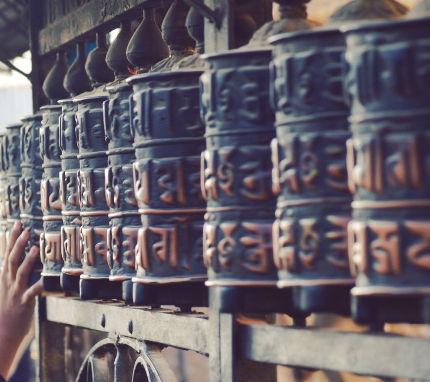 unrecognizable pilgrims touching prayer wheels in ancient temple in nepal