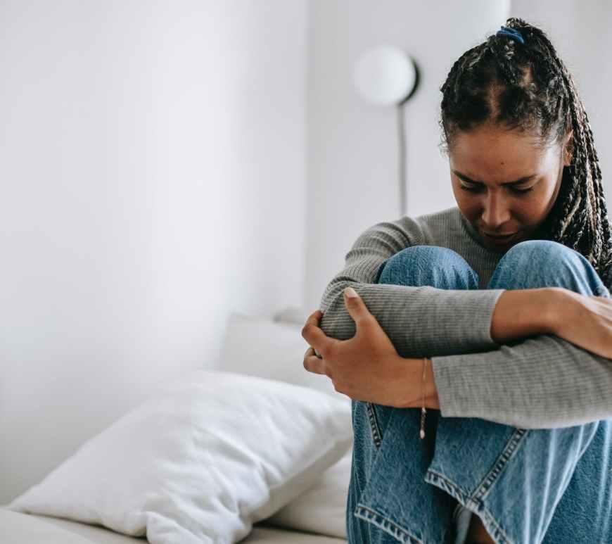 upset ethnic woman embracing knees on bed