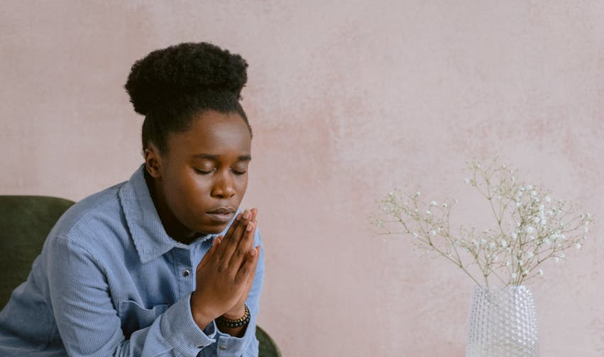 an afro haired woman sitting on a chair while praying