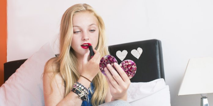 teenage girl in her bedroom putting on lipstick