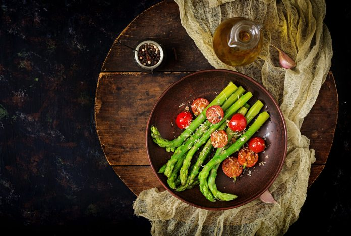 Vegan warm salad of roasted asparagus and tomatoes.