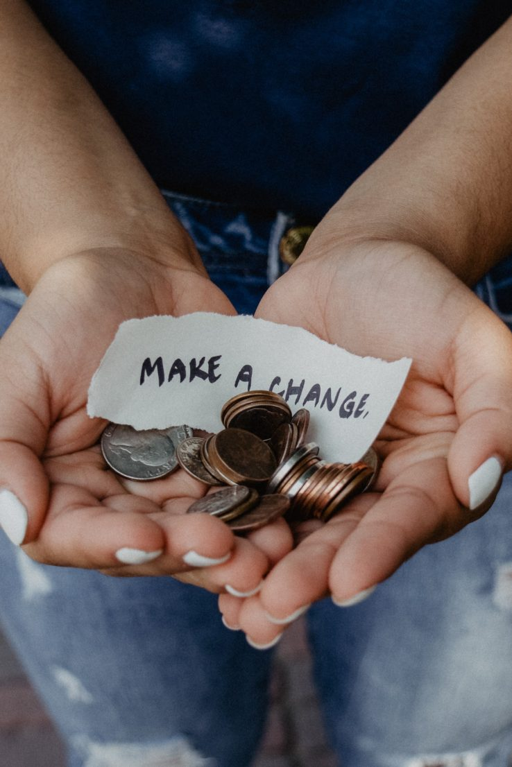 person holding coins with a sign that says make a change