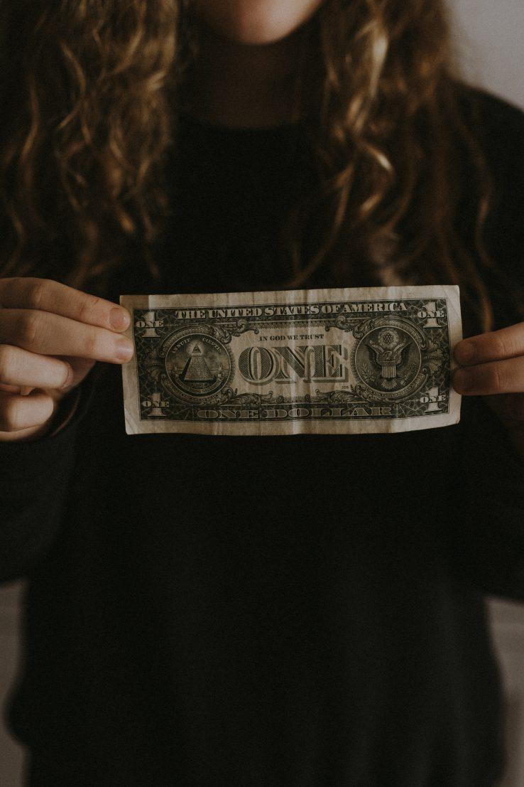 girl holding dollar bill