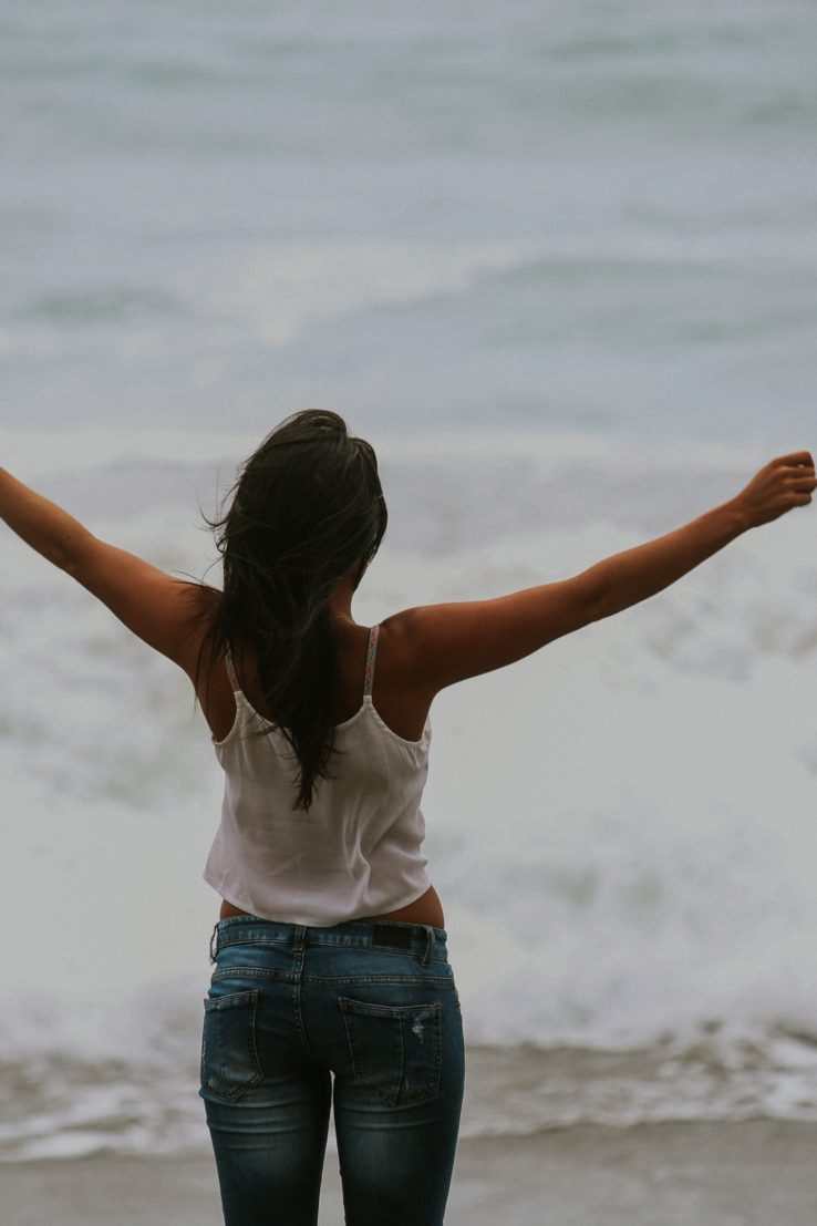 woman standing with arms raised facing the ocean
