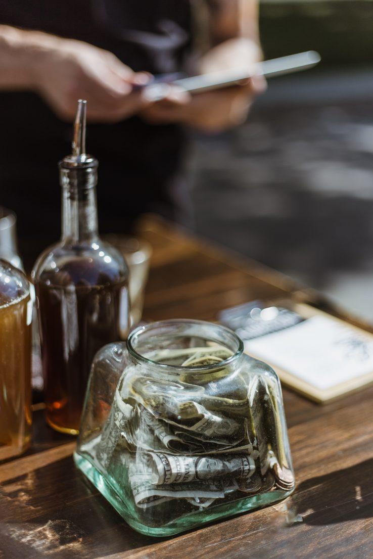 glass jar with dollar bills