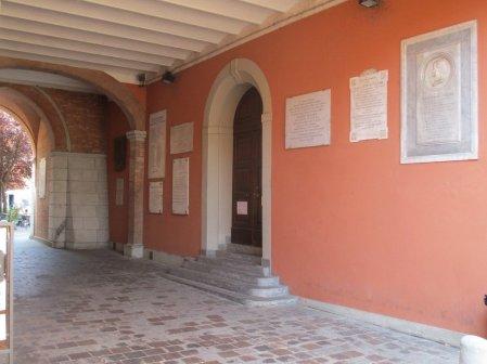 Il Voltone del Palazzo Comunale di Budrio: al centro della parete, acconto alla porta di ingresso, si può notare la lapide dedicata a Giuseppe Reggiani.